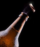 Top of open wet beer bottle. Isolated on black Stock Image