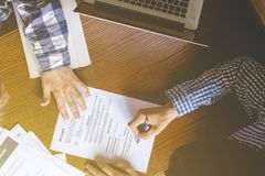 Top overhead directly above view of employee hiring person and examine the resume on the office table royalty free stock photo