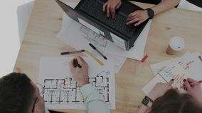 Top overhead view. Three creative design professionals intensely working with building project. Blueprint , male and. Female hands. Typing on laptop stock video footage