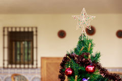 Top part of a Christmas tree with a star on top. Top part of a Christmas tree with a star over and some ornaments royalty free stock image