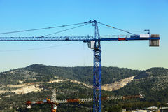 Rural Cranes. The top part of a tower crane raising above the hills in rural surroundings Stock Image