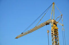 Top part of yellow tower crane, blue sky in background Stock Image