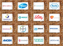 Top pharmaceutical companies logos and brands. Collection of logos and brands of most famous and popular pharmaceutical companies on white tablet on rusted Royalty Free Stock Photography