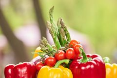 Top of a pile of vegetables, close up. Cluse up focused bell pepper and cherry tomatoes and blurred asparagus Royalty Free Stock Photo