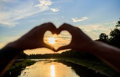 Top places for romantic date. Sunset sunlight romantic atmosphere. Male hands in heart shape gesture symbol of love and. Romance. Heart gesture in front of stock images