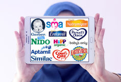 Top popular dry formula milk producers brands and logos. Arab muslim woman holding white tablet and most popular dry formula milk producers logos on display Royalty Free Stock Photography