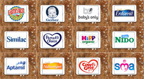 Top popular dry formula milk producers brands and logos. Collection of logos and vector of top famous dry formula milk companies on white tablet on rusty wooden Stock Photography