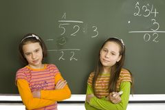 Top pupils. Two girls (11-13yo) are standing and looking at camera. Both are looking proud. There's greenboard with some maths exercise behind them stock image