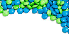 Top rame of blue green chocolate candy on white background. Top right frame of blue and green chocolate coated candy on white background with space for text Stock Photo