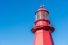 Top of a red lighthouse over blue sky in Gaspesie, Quebec La Ma Stock Photo