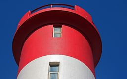 TOP OF RED AND WHITE LIGHTHOUSE IN SUNLIGHT. Close view of windows in a red and white lighthouse against a blue sky Stock Photo