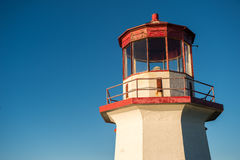 Top of a red and white old lighthouse over blue sky in Gaspesie,. Quebec Perc Stock Images