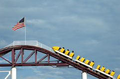 Top of a Roller Coaster. The cars of a roller coaster reaching the top peak with an American flag blowing Stock Image