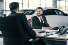 Top sales manager and customer at dealership showroom.  Royalty Free Stock Images