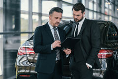 Top sales manager and customer at dealership showroom.  Stock Photo