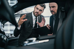 Top sales manager and customer at dealership showroom.  Stock Image