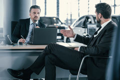 Top sales manager and customer at dealership showroom.  Royalty Free Stock Photos