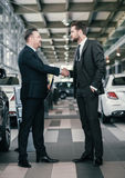 Top sales manager and customer at dealership showroom.  Stock Images