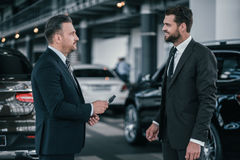 Top sales manager and customer at dealership showroom.  Stock Photography