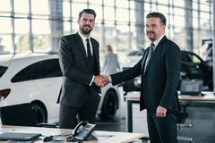 Top sales manager and customer at dealership showroom royalty free stock image