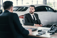 Top sales manager and customer at dealership showroom.  Royalty Free Stock Photography
