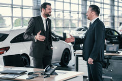 Top sales manager and customer at dealership showroom.  Royalty Free Stock Photo