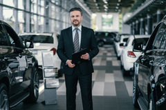 Top sales manager at dealership showroom.  Royalty Free Stock Photos