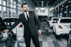 Top sales manager at dealership showroom.  Stock Images