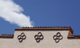 Top of  Santa Fe theater front with circle patterns against blue sky and white cloud. Royalty Free Stock Images