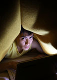 Top secret. Man in blanket using laptop on bed stock photography