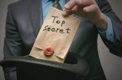 Top secret concept. Business man showing a Top secret documents or message in his hands. Top secret concept. Open the secret. Business man takes out secret Royalty Free Stock Photos