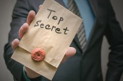 Top secret concept. Business man showing a Top secret documents or message in his hands. Top secret documents presentation concept. Top secret message in Royalty Free Stock Photos