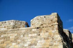 Part of antique castle wall from old sandy limestone and the canon on the top under clear blue sky ion sunny day. Top section of antique castle wall from old royalty free stock photography