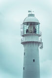 Top section (light) of a tall lighthouse. Maintenance session. Stock Photo