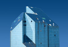 Top section of modern office building of glass and metal with some broken windows Stock Photos