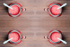 A top shallow dof view of a watermelon smoothies in a mason jars with tubes on wooden background Royalty Free Stock Photo