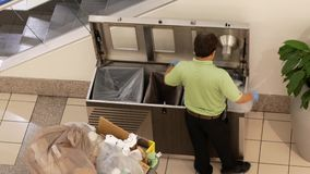 Top shot of cleaner changing garbage bag. Inside Buranby shopping mall stock footage