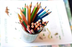 Top shot, close up of different, used, blunt, dull and sharpened colored pencils on bright papers background, space for text, stock images