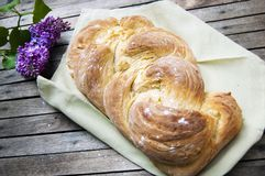 Top shot, close up of fresh baked homemade vegan braided loaf on a wooden, rustic table background, home baking, minimal Easter royalty free stock photography