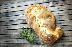 Top shot, close up of fresh baked homemade vegan braided loaf on a wooden, rustic table background, home baking, minimal Easter royalty free stock image