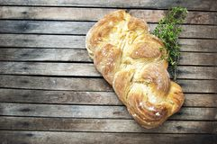 Top shot, close up of fresh baked homemade vegan braided loaf on a wooden, rustic table background, branches of thyme, home baking royalty free stock images