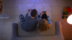 Top shot of couple plays videogame with joysticks disturbing each other by pressing the buttons in the living room. Top shot of couple plays videogame with stock video