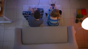 Top shot of couple in sleepwear playing videogame with joysticks on the floor gives five happily in the living room. Top shot of couple in sleepwear playing stock video footage