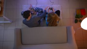 Top shot of couple in sleepwear plays videogame with joysticks disturbing each other on the floor in the living room. Top shot of couple in sleepwear plays stock video