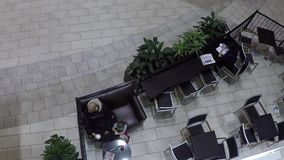 Top shot of customer drinking coffee inside mall. With wide angle shot stock footage