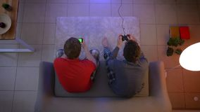 Top shot of friends in sleepwear playing videogame using joystick and working with smartphone in the living room. Top shot of friends in sleepwear playing stock video