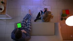 Top shot of girl in sleepwear playing videogame with joystick and guy watching into tablet and nodding in the living. Room stock footage