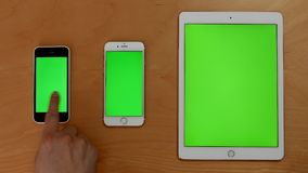 Top shot of hand touch phones and ipad on green screen. At home