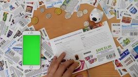 Top shot of man cutting coupon with various coupons background
