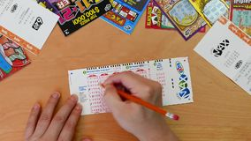 Top shot of man filling lucky number on lotto max ticket. With various lottery and scratch tickets background stock video
